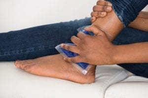 Person's Hand Holding Ice Gel Pack On Ankle